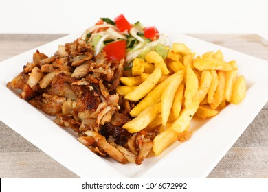Chicken doner on a plate with fries and salad