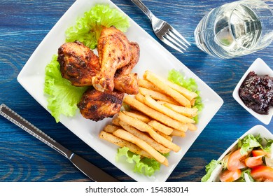 Chicken drumsticks with french fries. Selective focus
