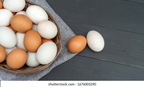 Chicken egg and duck egg on a black wooden table.