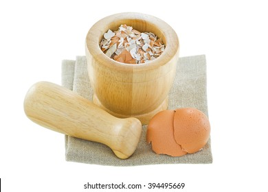 Chicken egg shells next to a wooden pestle and mortar with crushed shell inside isolated on white background.