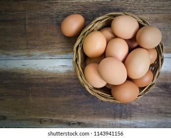 chicken eggs in basket on wooden background, Top view