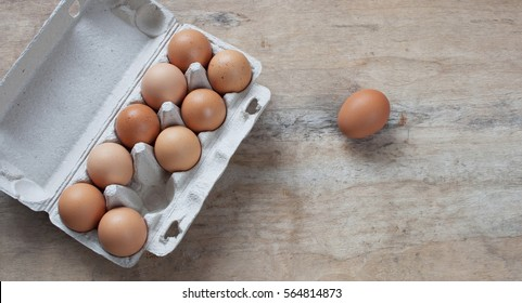 Chicken eggs in a cardboard box on a wooden table. Egg Yolk Cooking top type