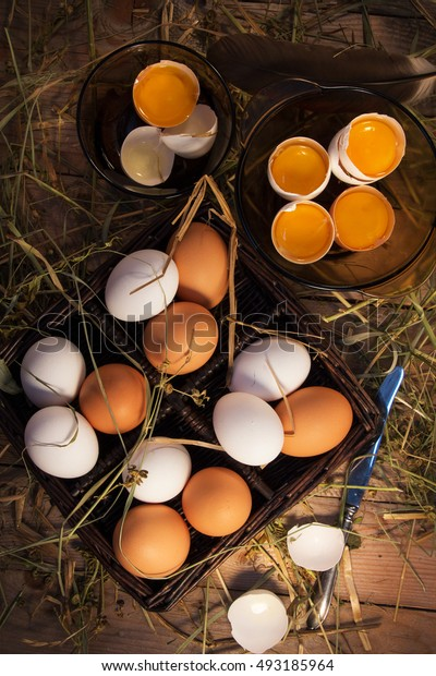 Chicken eggs homemade white and beige are in a wooden basket.