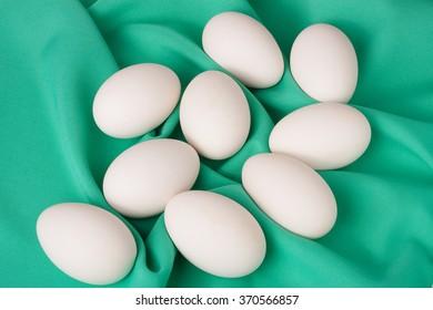 chicken eggs on green textile background.