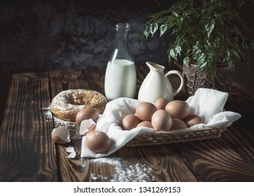 Chicken eggs on wooden boards with milk and a bun