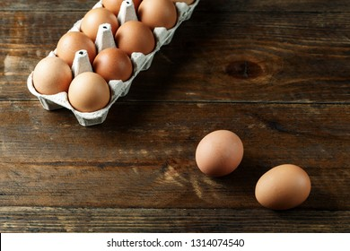 chicken eggs in a paper tray on wooden background. space for text