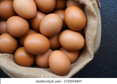 Chicken eggs in sack bag on black background.
