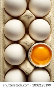 Chicken eggs with white shells in a carton container, top view, close-up