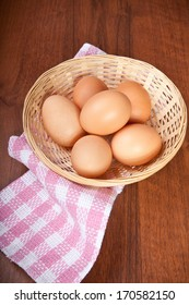Chicken eggs in a wicker basket on the table