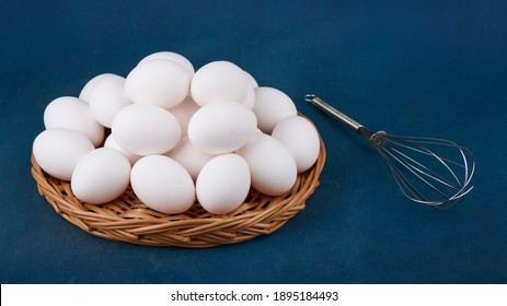Chicken eggs in wicker basket and whisk on blue background