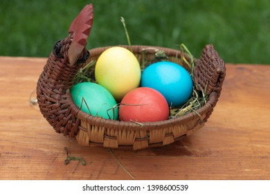 chicken eggs yellow, blue, red, green basket in the form of chicken on a brown board on a background of green grass bokeh