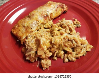 chicken and enchilada with cheese on red plate