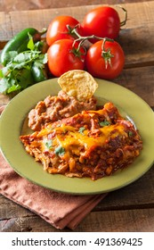 Chicken Enchilada Mexican Food Casserole Served On Rustic Green Plate On Vintage Wood Table Background, With Tomato, Jalapeno, Onion And Lime Fresh Ingredients.