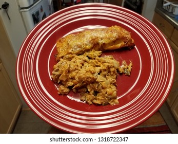chicken and enchilada on red plate in kitchen