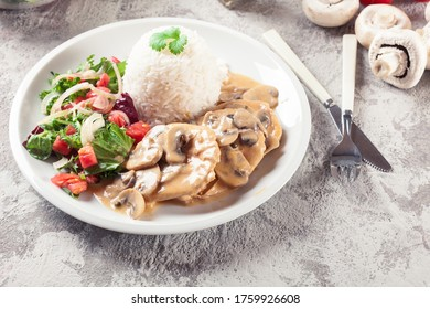Chicken escalopes with champignion in creamy sauce served with rice