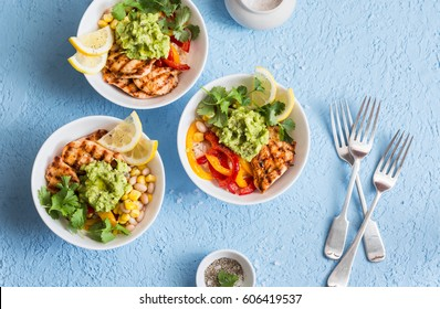 Chicken fajitas bowls on a blue background, top view. Flat lay