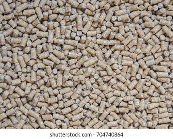 Chicken feed pellets as background.