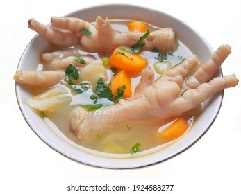 Chicken feet soup in a white bowl isolated on white background. Indonesian chicken feet soup with carrot, cabbage, and celery also known as sop ceker. Chicken feet and vegetable soup in a white bowl
