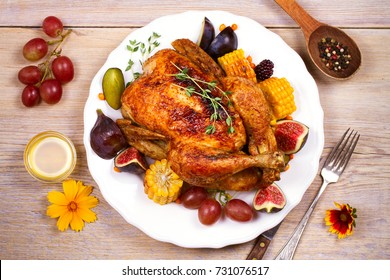Chicken with figs, corn on cob, grape, plums and blackberry, overhead