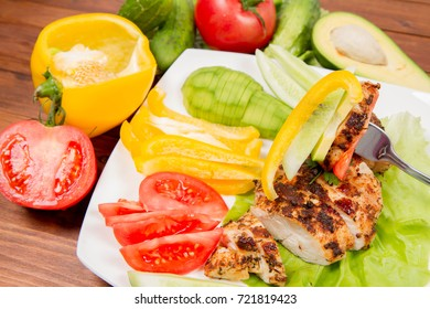 Chicken fillet with avocado and some vegetable on the side (tomato, cucumber, bell pepper) on a white background eaten with a fork