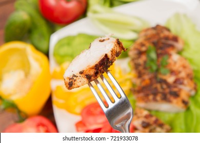 Chicken fillet with avocado and some vegetable on the side on a white background eaten with a fork