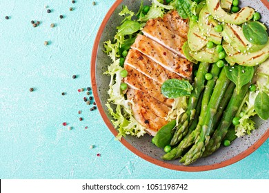 Chicken fillet cooked on a grill with a garnish of asparagus and grilled avokado. Dietary menu. Healthy food. Flat lay. Top view