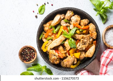 Chicken fillet fried with vegetables in frying pan. Chicken stir fry in wok. Top view on  white table with copy space.