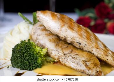 Chicken fillet in sauce with vegetables on a plate with roses in background