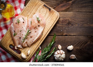 Chicken fillet with spices and rosemary on a dark wooden surface. Ingredients for cooking. Style rustic, copy space.