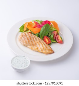 Chicken fillet steak with salad  and white sauce. Isolated on white background.
