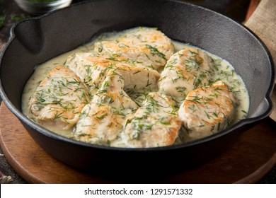 Chicken fillet or Turkey breast in creamy sauce with dill and garlic, in cast iron black pan on dark background with thick gravy. Delicious homemade food