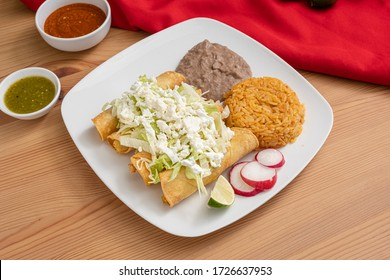 Chicken flautas served in an authentic Mexican restaurant. Fried rolled tortillas filled with meat and served with rice, beans, and salsa.