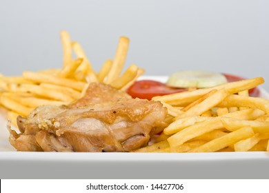 Chicken with French fries tomato plus onion isolated on white close-up