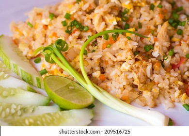 Chicken fried rice on white plate serve with lime, cucumber and spring onion