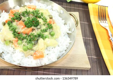 chicken frikassee with rice, peas, leeks and parsley in a pan