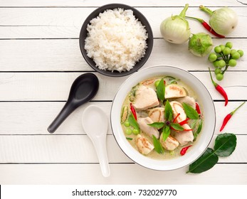 Chicken green curry with eggplant, sweet basil and hot chili  famous traditional  Thai food on white wooden table with copy space.