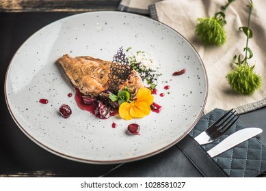 Chicken grilled fillet and berry sauce in a white plate. Fresh food close-up on a wooden table.