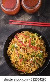 Chicken hakka noodles in black bowl placed on dark wooden background with red chopsticks.