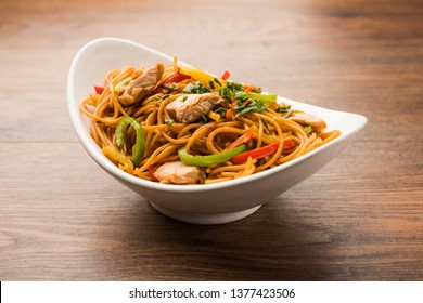 Chicken Hakka/Schezwan noodles served in a bowl with chopsticks. selective focus