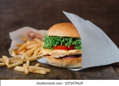 Chicken hamburger and french fries on wood background. Paper bag with empty place for title