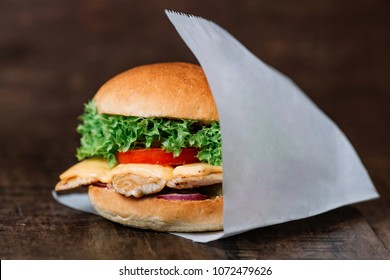 Chicken hamburger wrapped on white paper on wooden table. With empty place for title