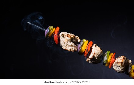 Chicken Hariyali kakab or Malai malai kebab in tricolour served with skewers and yogurt dip in a plate. selective focus