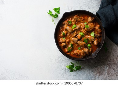 Chicken hearts stewed in tomato sauce in a skillet on gray stone background. Flat lay. Copy space