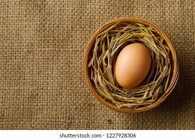 Chicken or hen egg on straw in wicker basket on sackcloth background