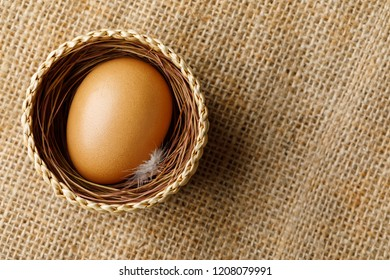 Chicken or hen egg in wicker basket on sackcloth background