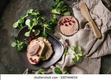 Chicken homemade liver paste or pate in glass jar with sliced whole grain bread, wood knife, cranberries, green salad served on ceramic plate with textile over dark metal background. Top view, space