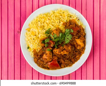 Chicken Jalfrezi Curry With Basmati Spiced Rice Against a Pink Wooden Background