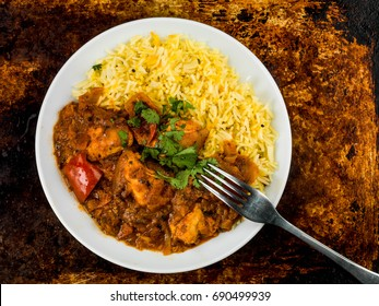 Chicken Jalfrezi Curry With Basmati Spiced Rice Against a Distressed Oven or Baking Tray