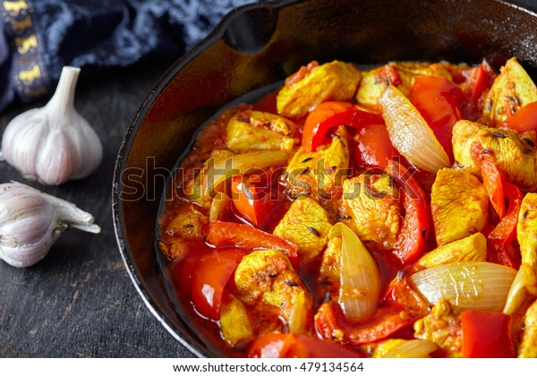 Chicken jalfrezi Indian culture fried spicy curry chilli sauce meat and vegetables healthy dietetic food dish in cast iron pan on vintage wooden table background.