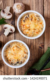Chicken julienne and mushrooms in portion forms on a wooden table, selective focus